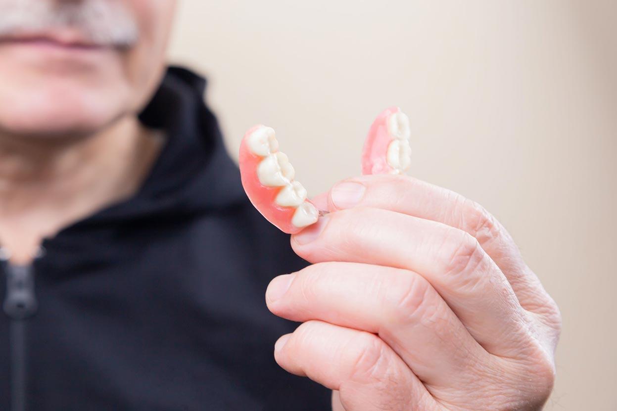Man Holding Dentures
